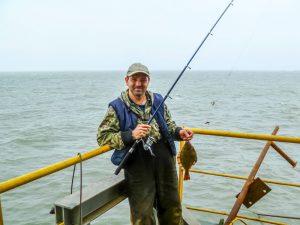 fisherman holding a flounder aka fluke